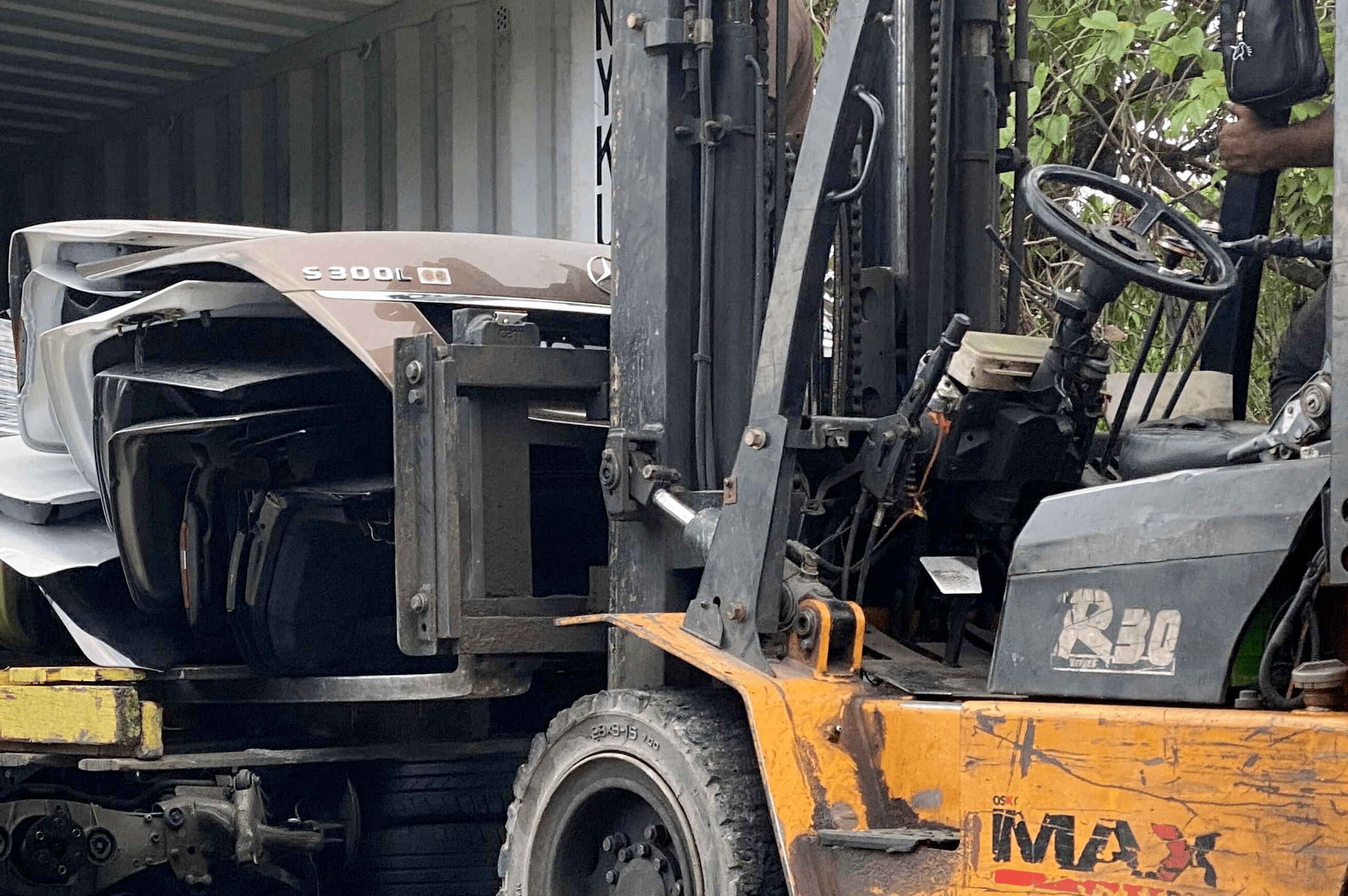 forklift lifting scrapped car parts into container