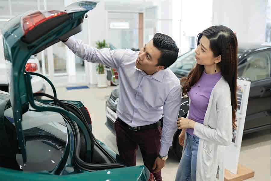 asian couple checking trunk of car for comparison and research