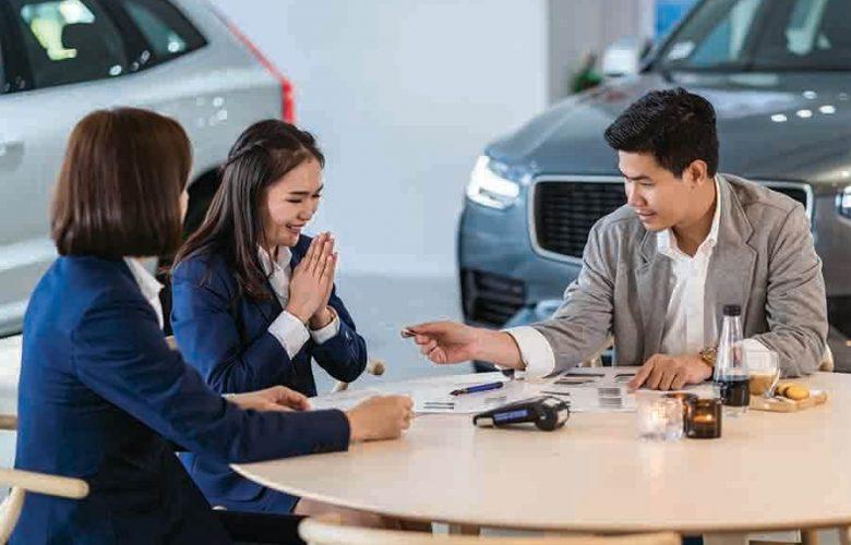 asian women at a car showroom purchasing a new car