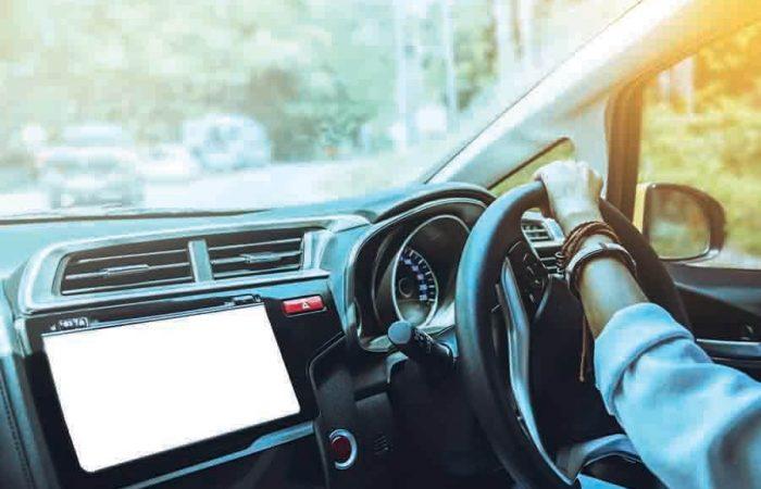 women's hand on the steering wheel making a turn