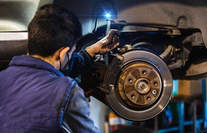 mechanic changing car brakes